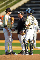 Wake Forest Demon Deacons pitching coach Dennis Healy #31 chats with pitcher Chris Willson #91 and catcher Charlie Morgan #26 during the game against the UNC-Asheville Bulldogs at Wake Forest Baseball Park on February 28, 2012 in Winston-Salem, North Carolina.  The Demon Deacons defeated the Bulldogs 9-8.  (Brian Westerholt/Four Seam Images)