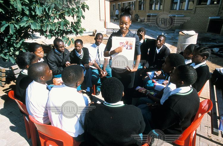 A sex education class at a secondary school. A teacher talks to students about sexually transmitted diseases (STDs).