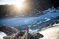 A woman hiking up rock above the Glacier de Corbassière, with a serac field below, on the way to the Combin de Corbassière, Switzerland
