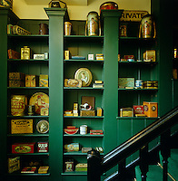 A collection of classic tins from the 19th and 20th century are displayed on painted green shelving that runs along the staircase