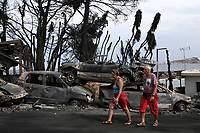 Pictured: Two local people walk next to piles of destroyed cars in the aftermath of the forest fire which has claimed dozens of lives in the Mati area of Rafina, Greece. Tuesday 24 July 2018<br /> Re: Deaths caused by wild forest fires throughout Greece.