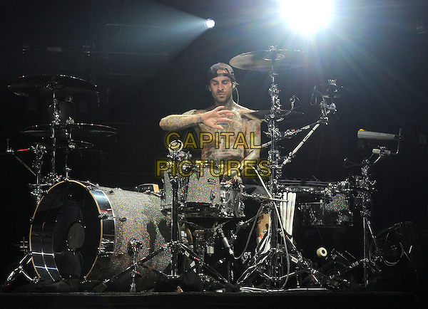 BLINK-182 - Travis Barker .performs live in at The Hollywood Palladium in Hollywood, California, USA, October 10th 2009..music concert band group gig on stage playing performing half length topless chest tattoos drums drummer cap hat hand arm                                                     .CAP/DVS.©DVS/RockinExposures/Capital Pictures