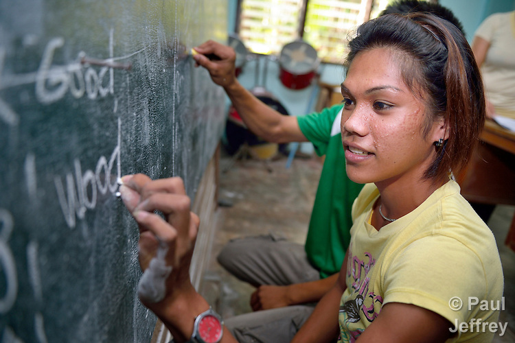 A woman writes on the blackboard as she participates in an adult literacy class in the village of Magsaysay, in New Bataan in the Compostela Valley on Mindanao Island in the southern Philippines.