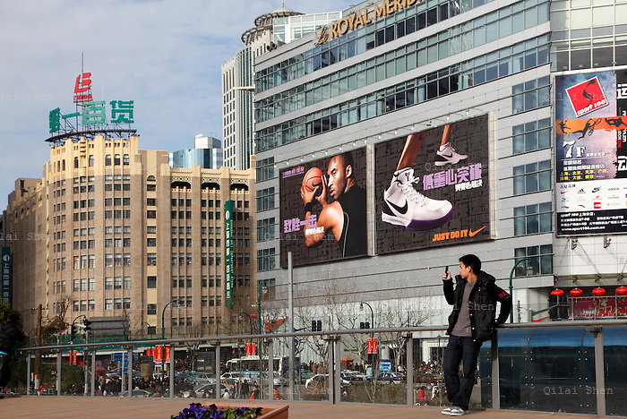 A man takes a picture with his cellphone while standing in People's Park near the Nanjing Road pedestrian shopping street in downtown Shanghai, China on 28 January 2009.  A vestige of the old planned economy days, the No. 1 Department Store and the new symbol of the capitalist west, the Nike flagship store featuring a giant billboard of NBA start Kobe Bryant, stand in the back ground.