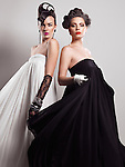 Fashion photo of two women with beautiful creative hairstyles wearing long black and white dresses