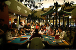 Phnom Penh's Nagaworld Casino and five-star hotel is one of Cambodia's biggest private employers with more than 3,000 staff catering for a stream of visitors. It functions non-stop 24 hours a day with an inside airconditioned controlled temperature of 21 degrees.It is a 14 storey hotel and entertainment complex, with more than 500 bedrooms, 14 restaurants and bars, 700 slot machines and 200 gambling tables. There is also a spa, karaoke and VIP suites, live bands, and a nightclub. Its monolithic building dominates the skyline at the meeting point of the Mekong and Tonle Sap rivers, in stark contrast to nearly intricate Khmer architecture.///Guests gambling with croupier with her back to us in Nagaworld casino
