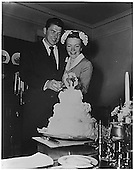 Photograph of Newlyweds Ronald Reagan and Nancy Reagan cutting their wedding cake,  March 4, 1952..