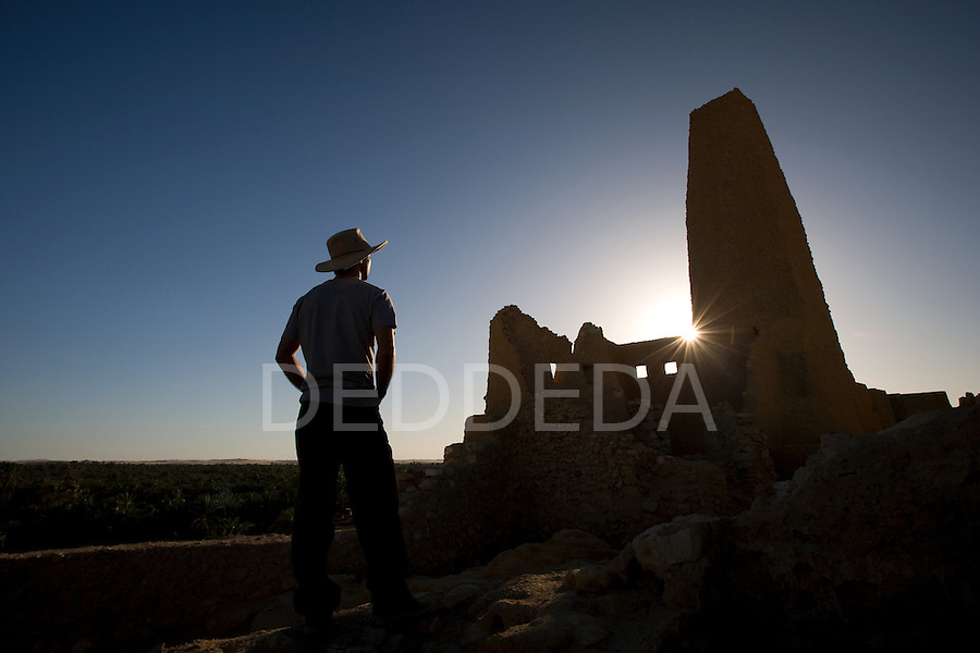 A male tourist stands within the Temple of the Oracle, dedicated to Amun, which was built in the 6th century BC and is one of the most revered oracles in the ancient Mediterranean. The Temple sits in the ruins of Aghurmi village in the Siwa Oasis, Egypt. Alexander the Great consulted the priests of Amun at the Temple of the Oracle in 331 BC.