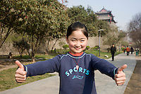 Girl playing in the park by the City Wall, Xian. China has a one child policy to limit population.