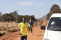 Renato Canova coaches elite Kenyan runners in the high altitude town of Iten. Here he monitors Abel Kirui's time from his pace car during a training run outside Iten, Kenya.