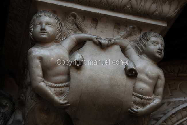 Putti holding a scroll, from the tomb of the Cardinals of Amboise, 1515-25, by Roullant Le Roux and Pierre des Aubeaux in Renaissance style, in Rouen Cathedral or the Cathedrale de Notre Dame de Rouen, built 12th century in Gothic style, with work continuing through the 13th and 14th centuries, Rouen, Normandy, France. The tomb has 2 praying figures of Cardinal Georges d'Amboise, died 1510, archbishop of Rouen, and his nephew Georges II d'Amboise, died 1550, also archbishop and cardinal. Below are 6 statues representing faith, charity, prudence, power, justice and temperance. Picture by Manuel Cohen