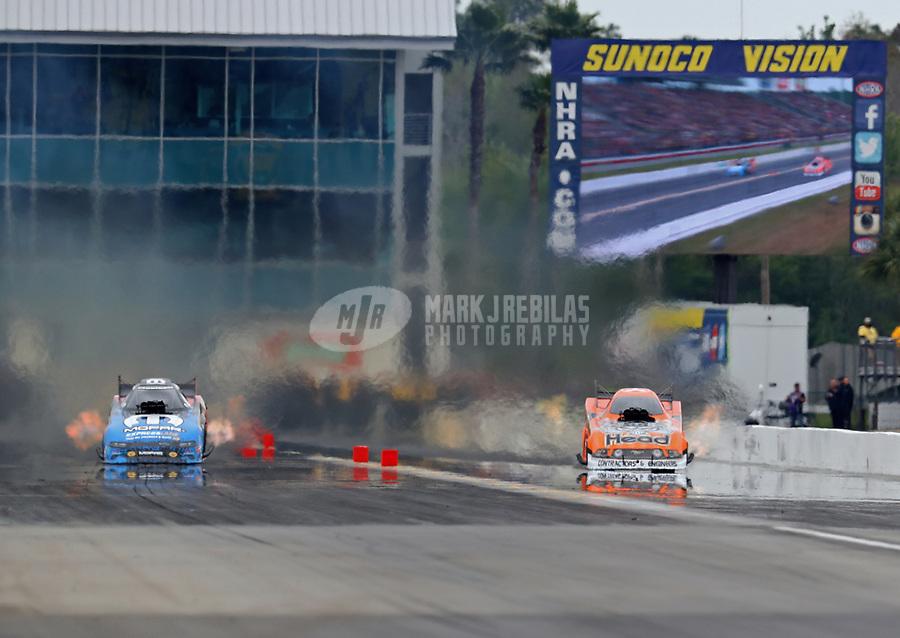 Mar 17, 2019; Gainesville, FL, USA; NHRA funny car driver Matt Hagan (left) races alongside Jonnie Lindberg during the Gatornationals at Gainesville Raceway. Mandatory Credit: Mark J. Rebilas-USA TODAY Sports