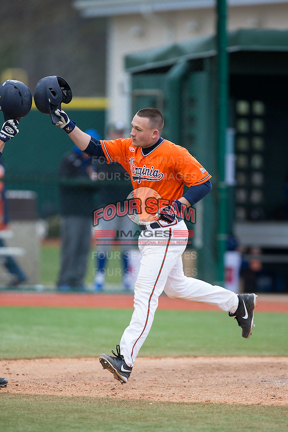 Matt Thaiss (21) of the Virginia Cavaliers knocks helmets with a teammate after hitting a home run against the Seton Hall Pirates at The Ripken Experience on February 28, 2015 in Myrtle Beach, South Carolina.  The Cavaliers defeated the Pirates 4-1.  (Brian Westerholt/Four Seam Images)