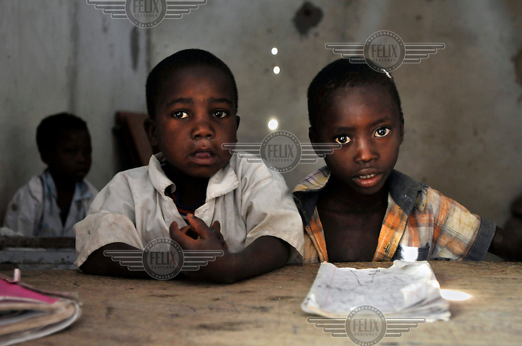 Two children share a desk in a class at the Lumege-Canjamba primary school. The area around the school was contaminated with landmines during Angola's long civil war, preventing many children from coming to school and limiting the movement of those who did. The Mines Advisory Group (MAG) cleared the area of mines and other remnants of war allowing children to receive an education safely and for plans to build more class rooms to accommodate an increasing number of students who are arriving under the government's Village Reunification Program, that encourages families living in remote hamlets to move to larger villages so that the government can provide basic services such as education, health care, water and electricity.