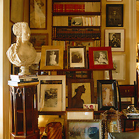 Framed paintings and photographs displayed on and around an easel in a corner of the drawing room
