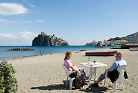 ITA, Italien, Kampanien, Ischia, vulkanische Insel im Golf von Neapel: Paar, leerer Strand zur Vorsaison, im Hintergrund das Castello Aragonese | ITA, Italy, Campania, Ischia, volcanic island at the Gulf of Naples: couple, secluded beach at off season, Castello Aragonese at background