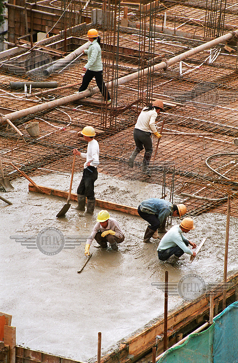 Construction workers cementing the roof of a building.