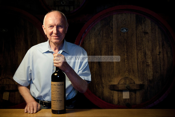 Giuseppe Quintarelli, Valpolicella's legendary winemaker, in his cellar with a bottle of Amarone della Valpoliclla, Veneto, Italy