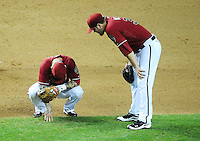May 9, 2012; Phoenix, AZ, USA; Arizona Diamondbacks third baseman Ryan Roberts (left) reacts in pain as pitcher Wade Miley looks on in the fifth inning against the St. Louis Cardinals at Chase Field. Mandatory Credit: Mark J. Rebilas-