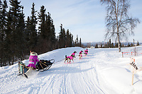 Dee Dee Jonrowe runs uphill towards the village checkpoint of Ruby during the 2010 Iditarod
