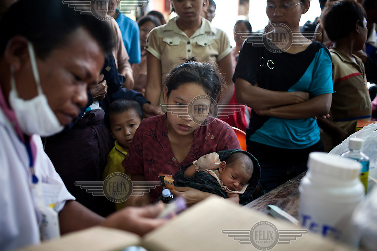 A woman brings her 4 month old child to a doctor in a refugee camp. An estimated 20,000 Burmese refugees fled into Thailand to escape clashes in the border towns of Myawaddy and Pyaduangsu, only a day after a Burmese election which critics described as a sham..Ethnic minorities along the Thai-Burma border had warned earlier that the junta would launch a major offensive after the election, as many armed rebel groups had refused to become part of the government-controlled Border Guard Forces.
