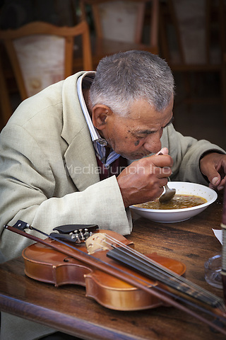 A street musician drinking soup at a restaurant table, Nessebar, Bulgaria  June 2015.<br /> CAP/MEL<br /> &copy;MEL/Capital Pictures /MediaPunch ***NORTH AND SOUTH AMERICA ONLY***