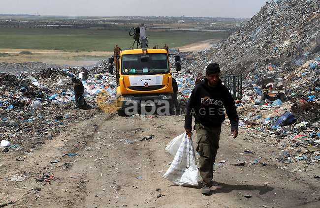 Palestinian workers search in the garbage near the border with Israel, east of Rafah town, in the southern Gaza Strip, April 16, 2015. Workers collect the household recyclables, metals and plastic from landfill and garbage to sell to the Israeli and local factories. Photo by Abed Rahim Khatib