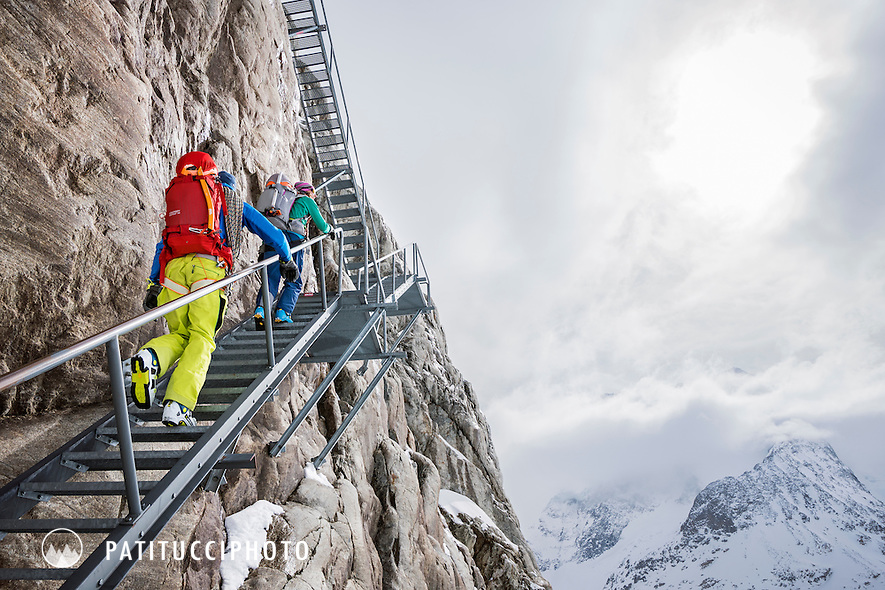 Ski tourers climbing the long stairs to the Konkordia Hut while on a ski tour of the Berner Oberland, Switzerland. The stairs allow access to the hut which once sat on the edge of the glacier, but now sits well above the Aletschgletscher.