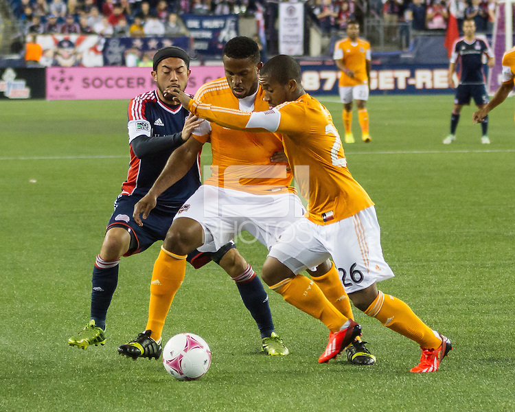 Houston Dynamo defender Jermaine Taylor (4) blocks New England Revolution midfielder Lee Nguyen (24) as Houston Dynamo defender Corey Ashe (26) prepares to clear the ball.  The New England Revolution played to a 1-1 draw against the Houston Dynamo during a Major League Soccer (MLS) match at Gillette Stadium in Foxborough, MA on September 28, 2013.
