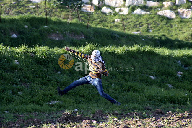A Palestinian protester hurls stones at Israeli security forces during clashes at Hawwara military checkpoint near the West Bank city of Nablus on February 26, 2013. Increased protests in the West Bank after the killing of a Palestinian Prisoner Arafat Jaradat, 30, whose death in an Israeli jail on 23 February sparked riots across the Israeli-occupied West Bank. Palestinians claim he died of torture. Israel says the initial autopsy could not determine the cause of death and further tests were needed. Photo by Nedal Eshtayah