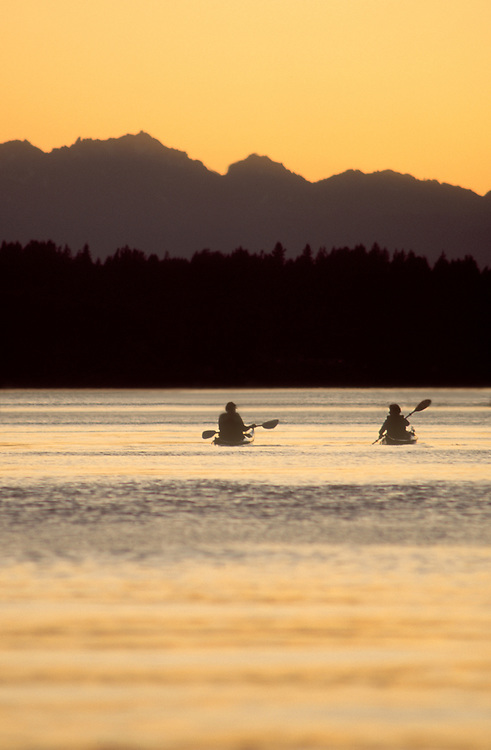 Sea Kayakers, Puget Sound, Olympic Mountains, couple off Blake Island Marine State Park at sunset, Seattle, Washington State, Pacific Northwest, USA,.