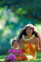 A beautiful Polynesian woman with her daughter, both dressed in colorful aloha wear and wearing plumeria and haku leis, sit smiling together on the grass.