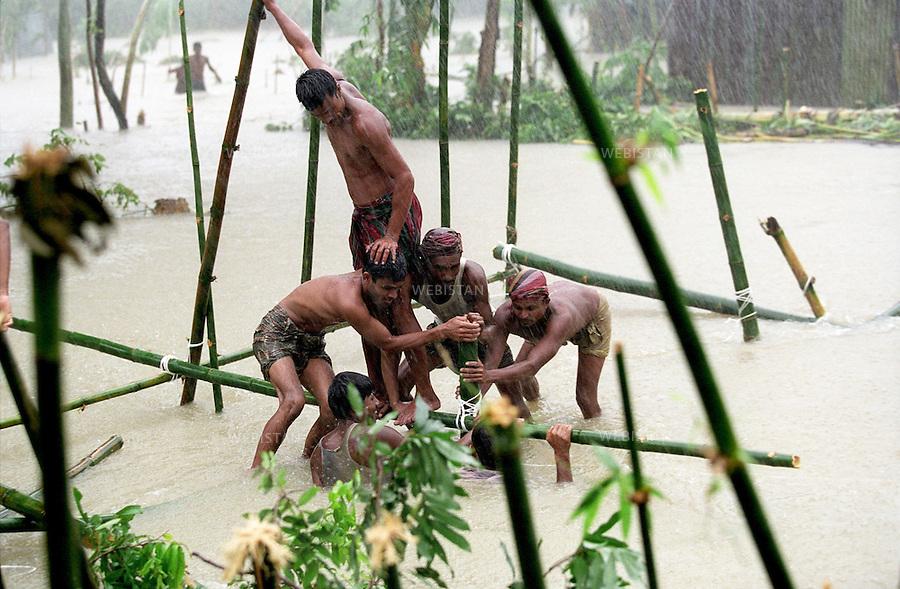 2004. Villagers build a raft out of bamboo shafts in the middle of floodwater in Gosai Bari. Des villageois construisent un radeau avec des bambous au milieu des eaux de l'inondation à Gosai Bari.