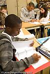 Public Middle School Grade 8 male student at work female teacher working with male student in background vertical
