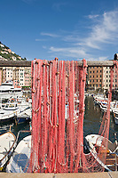 Fishing net hangs to dry in harbour, Camogli, Liguria, Italy