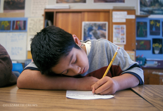 Berkeley CA 5th grade Latino boy doing independent writing in class