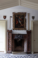 The entrance hall's eclectic chimneypiece has a baroque influenced relief and medieval-style tower piers, which echo Huntington's crenellated roofline