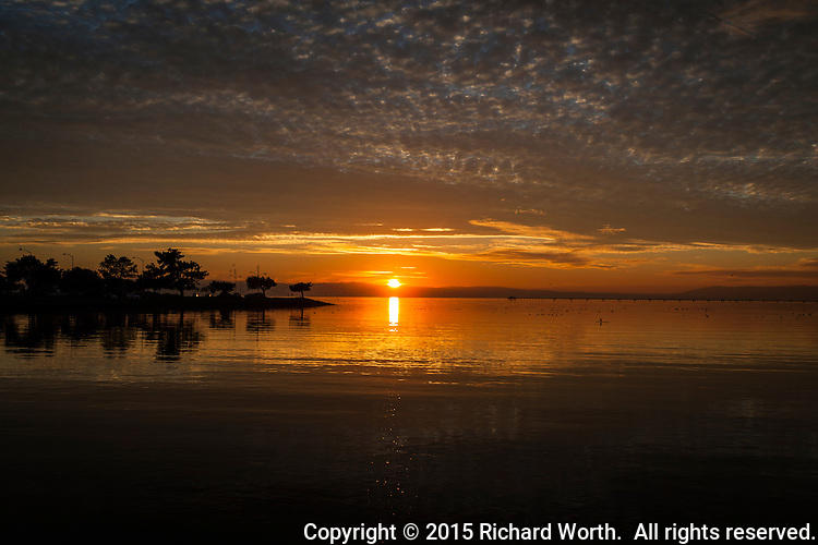 A golden orange sunset glow bathes sky, land and water moments before the sun slides from view along the eastern shore of San Francisco Bay.