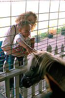 Mom and son age 4 and 25 touching pony at State Fair petting zoo.  St Paul Minnesota USA
