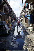 A man walks over an alley filled with collected rain water in Sitio Aroma in Barangay 105, Manila in Philippines. Photo: Sanjit Das