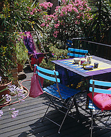 Colourful textiles, crockery and garden furniture combine to bring this small terrace to life