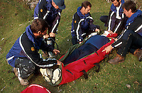 Mountain rescue team with a climber that has fallen down onto rocks. They have placed the casualty in a vacum mattress and immobilised his neck in a cervical splint prior to evacuation. This image may only be used to portray the subject in a positive manner..©shoutpictures.com..john@shoutpictures.com