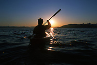 Kayaker paddles into the sunset in Prince William Sound, Alaska.
