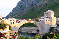 View along the river of the old reconstructed bridge. Sunset late afternoon light.. Cafes restaurants in the foreground. Historic town of Mostar. Federation Bosne i Hercegovine. Bosnia Herzegovina, Europe.