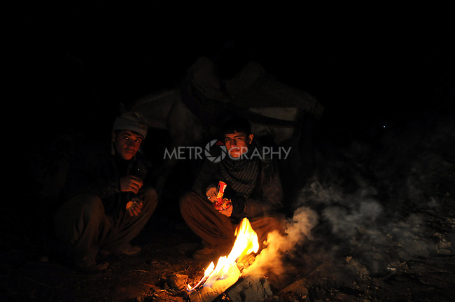 BASHMAKH, IRAQ: Iranian Kurdish smugglers warm themselves by a fire while they wait for night to fall...Iranian Kurdish smugglers traffic petrol from Iran into Iraq and alcohol from Iraq into Iran.  On foot, a smuggler can look to make around $10 per trip whereas with a horse a smuggler can make $100.  The routes are very dangerous with the risk of stepping on land mines or  being shot by the Iranian military..Photo by Kamaran Najm/Metrography