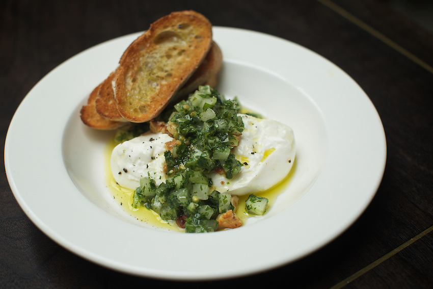 NEW YORK, NY - May 3, 2016: Burrata with green tomato salsa verde &amp; walnuts at Metrograph Commissary. The new restaurant at Lower East Side movie theater, Metrograph opens on Thursday, May 5th.<br /> <br /> CREDIT: Clay Williams for New York Magazine.<br /> <br /> &copy; Clay Williams / claywilliamsphoto.com