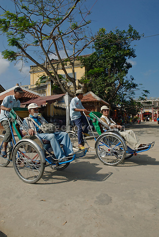 Asia, Vietnam, Hoi An. Hoi An old quarter. Cyclo drivers having japanese senior passengers. The historic buildings, attractive tube houses, and decorated community halls have 1999 earned Hoi An's old quarter the status of a UNESCO World Heritage Site. To protect the old quarter's character stringent conversation laws prohibit alterations to buildings, as well as the presence of cars on the roads.