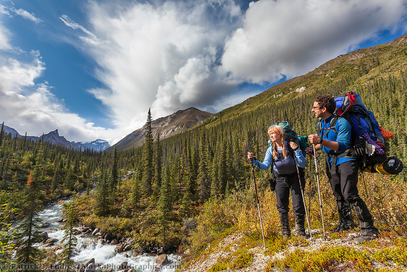 Backpackers pause along the Arrigetch creek, Elephants tooth mountain in the distance, Arrigetch Peaks, Gates of the Arctic National park, Alaska.