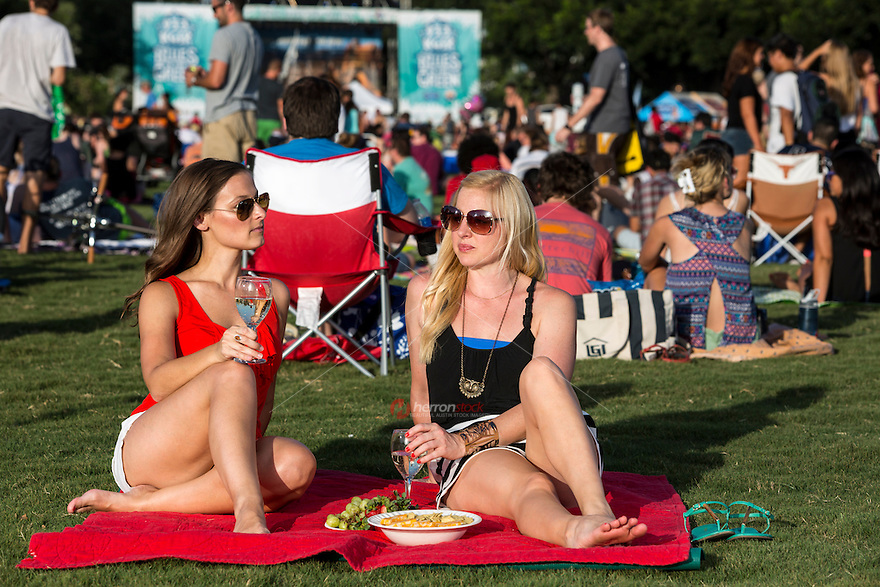 Two fit attractive women sit on a blanket drinking wine at the Blues On The Green free summertime concerts in Zilker Park, Austin, Texas. Blues On The Green is series of free summertime concerts hosted by KGSR Austin Radio and held in Austin's Zilker Park.
