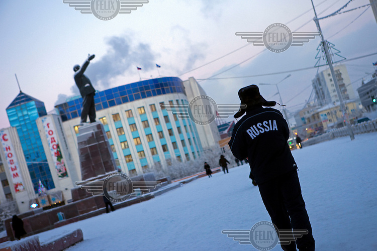 A man stands near a statue of Lenin in Lenin Square in the city centre of Yakutsk. Yakutsk is one of the coldest cities on earth, with winter temperatures averaging -40.9 degrees Celsius.